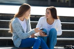 Dos adolescentes femeninos felices que hablan junto en la calle Foto de archivo libre de regalías