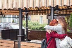 Dos adolescentes femeninos que abrazan en el café de la calle de la ciudad Foto de archivo libre de regalías