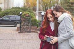 Dos adolescentes femeninos que buscan las noticias en el smartphone en t Foto de archivo