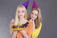 Dos adolescentes hermosos con la torta de cumpleaños Imágenes de archivo libres de regalías