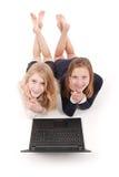 Dos adolescentes hermosos que mienten en piso y Internet que practica surf en el ordenador portátil Foto de archivo