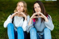 Dos adolescentes hermosos Verano en naturaleza Después de escuela en la escuela Se están sentando en hierba Gestos de la demostra Fotografía de archivo