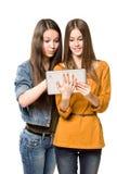 Adolescentes que se divierten con un ordenador de la tableta. Fotos de archivo libres de regalías