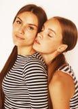 Dos adolescentes lindos que se divierten junto aislada en blanco Fotos de archivo libres de regalías