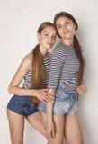 Dos adolescentes lindos que se divierten junto aislada en blanco Foto de archivo