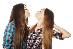 Dos adolescentes lindos que se divierten junto aislada en blanco Imagen de archivo libre de regalías