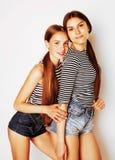 Dos adolescentes lindos que se divierten junto aislada en blanco Imágenes de archivo libres de regalías