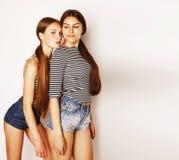 Dos adolescentes lindos que se divierten junto aislada en blanco Imagenes de archivo
