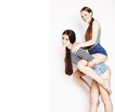 Dos adolescentes lindos que se divierten junto aislada en blanco Fotografía de archivo libre de regalías