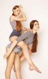 Dos adolescentes lindos que se divierten junto aislada encendido Imagen de archivo