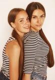 Dos adolescentes lindos que se divierten junto aislada encendido Imagen de archivo libre de regalías