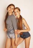 Dos adolescentes lindos que se divierten junto en blanco Foto de archivo libre de regalías