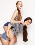 Dos adolescentes lindos que se divierten junto en blanco Imagen de archivo libre de regalías