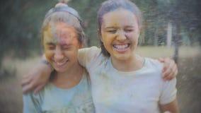 Dos adolescentes manchados con el polvo coloreado Holi asperjan el agua en el parque del verano en la cámara lenta metrajes