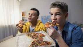 Dos adolescentes masculinos multiétnicos que comen la pizza y que miran al programa de televisión, tiempo libre almacen de video