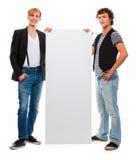 Dos adolescentes modernos que sostienen la cartelera en blanco Imagen de archivo libre de regalías