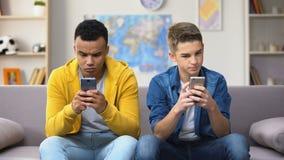 Dos adolescentes multirraciales que enrollan los smartphones que se ignoran, apego metrajes