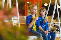 Dos adolescentes o niños felices - jugo de consumición del muchacho y de la muchacha en café Fotografía de archivo