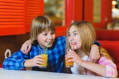 Dos adolescentes o niños felices - jugo de consumición del muchacho y de la muchacha en café Imágenes de archivo libres de regalías