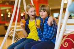 Dos adolescentes o niños felices - jugo de consumición del muchacho y de la muchacha en café Imagenes de archivo