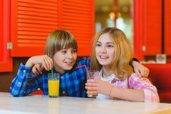 Dos adolescentes o niños felices - jugo de consumición del muchacho y de la muchacha en café Imagen de archivo