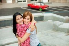 Dos adolescentes que abrazan en la calle Fotos de archivo libres de regalías