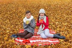 dos adolescentes que beben el té que se sienta en una tela escocesa en un campo del bosque del otoño Fotos de archivo