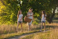 Dos adolescentes que caminan con la madre en campo en la puesta del sol Fotografía de archivo