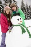 Dos adolescentes que construyen el muñeco de nieve el día de fiesta del esquí Fotos de archivo