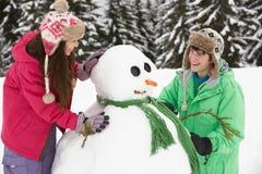 Dos adolescentes que construyen el muñeco de nieve el día de fiesta del esquí Imagen de archivo libre de regalías