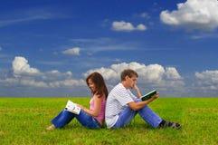 Dos adolescentes que estudian al aire libre en hierba Foto de archivo