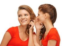 Dos adolescentes que hablan en camisetas rojas Imagen de archivo libre de regalías