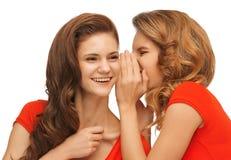 Dos adolescentes que hablan en camisetas rojas Foto de archivo