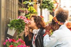 Dos adolescentes que huelen las flores fotografía de archivo