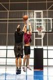 Dos adolescentes que juegan al baloncesto junto en la corte Imagenes de archivo