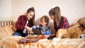 Dos adolescentes que juegan con su hermano del niño con los juguetes en cama Fotos de archivo
