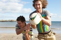 Dos adolescentes que juegan a rugbi en la playa Imágenes de archivo libres de regalías