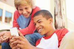 Dos adolescentes que leen el texto en el teléfono móvil Fotografía de archivo