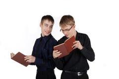 Dos adolescentes que leen un libro en el fondo blanco Fotografía de archivo