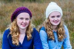Dos adolescentes que llevan los sombreros en naturaleza Imagen de archivo libre de regalías