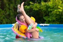 Dos adolescentes que se divierten en la piscina Fotografía de archivo libre de regalías