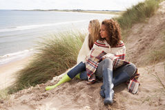 Dos adolescentes que se sientan en dunas de arena Foto de archivo libre de regalías
