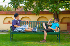 Dos adolescentes que se sientan en el banco y lanzar Imágenes de archivo libres de regalías