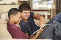 Dos adolescentes que se sientan en el ordenador de Sofa At Home Using Tablet Fotografía de archivo libre de regalías