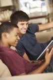 Dos adolescentes que se sientan en el ordenador de Sofa At Home Using Tablet Imagen de archivo