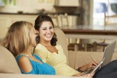 Dos adolescentes que se sientan en el ordenador y el ordenador portátil de Sofa At Home Using Tablet Fotografía de archivo