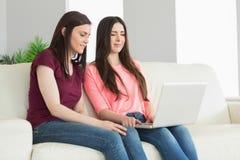 Dos adolescentes que se sientan en un sofá y que miran un ordenador portátil Foto de archivo libre de regalías