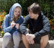 Dos adolescentes que se sientan y que hablan Fotos de archivo libres de regalías