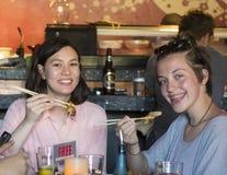 Dos adolescentes que sostienen la comida con los palillos Imagen de archivo libre de regalías