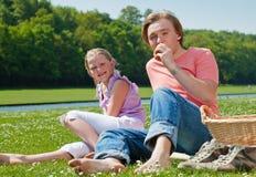 Dos adolescentes que tienen comida campestre Fotografía de archivo